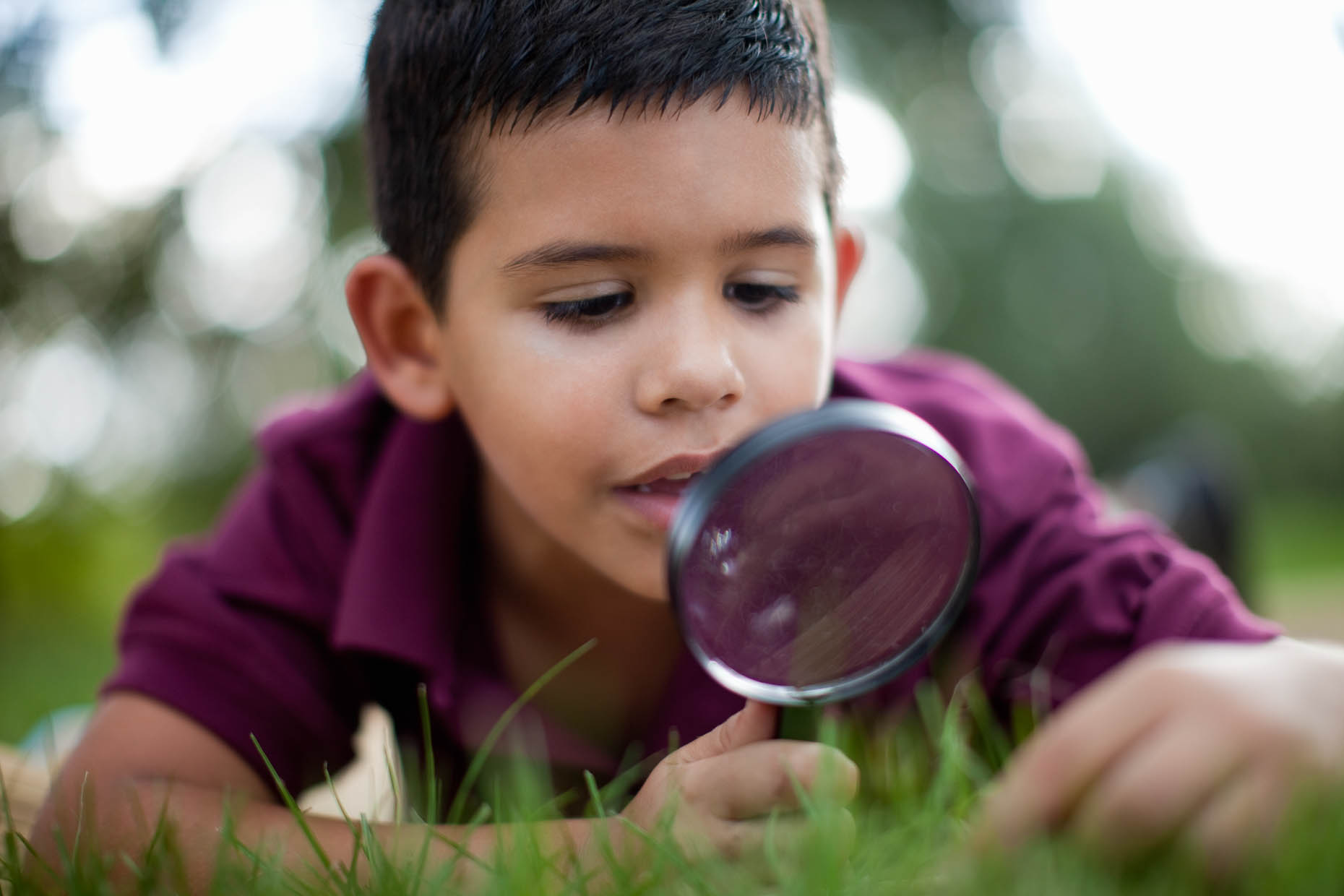 Hispanic-boy-in-grass-with-magnifier