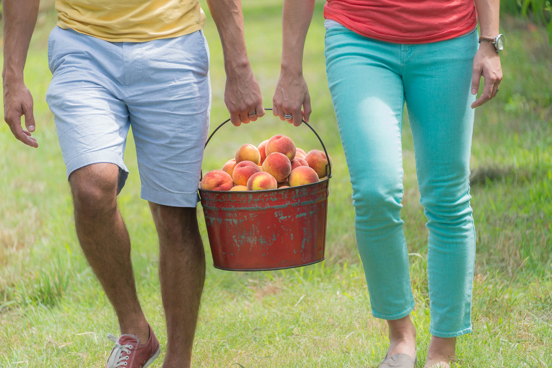 Young-couple-carrying-bucket-of-peaches